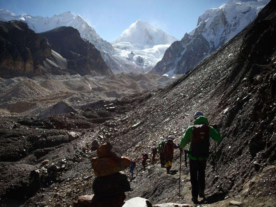 Alpinisten laufen über Moränengelände.