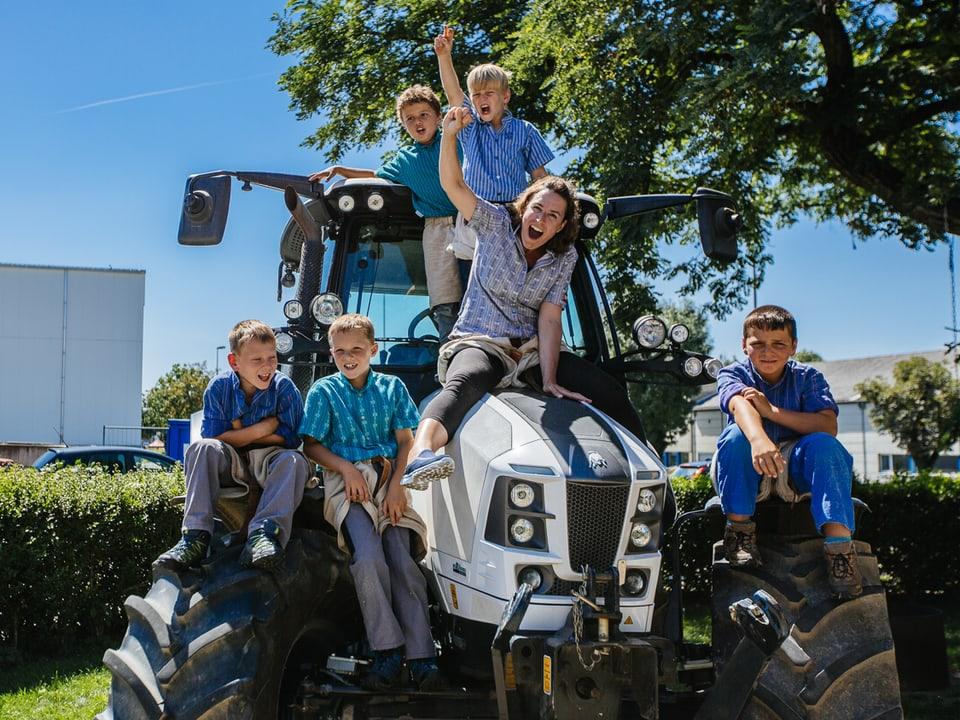 Joëlle Beeler posiert mit ihren Jungschwingern auf einem Traktor.