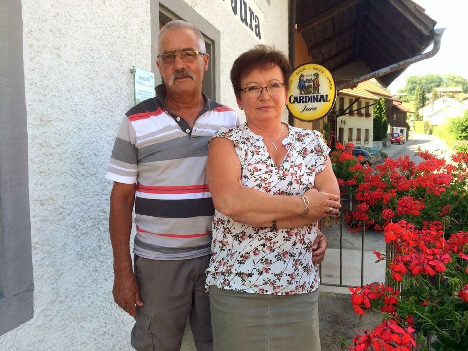 Ein Ehepaar steht vor dem Eingang seines Restaurants.