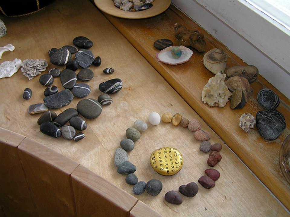 Fensterbrett mit gefundenen Steinen, einige sind im Kreis ausgelegt und bilden mit ihren natürlichen Farben den Farbkreis nach.