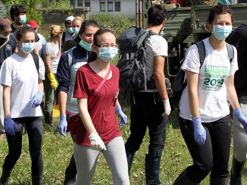 Mit Atemschutzmasken versehene Studenten sind auf dem Weg zu einem Reinigungseinsatz.
