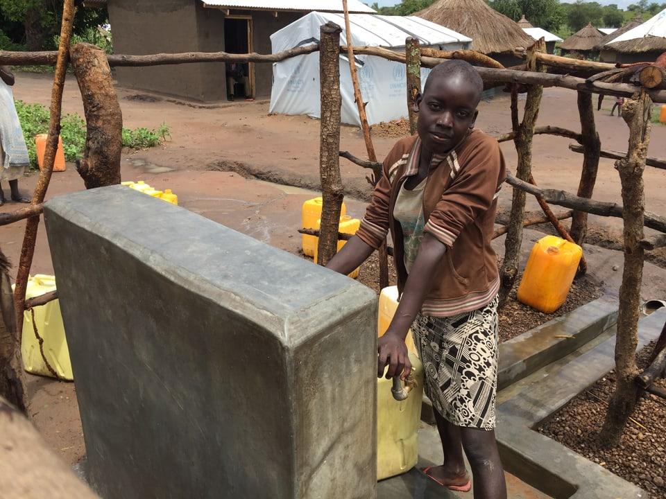 Junge Frau an einem Brunnen.