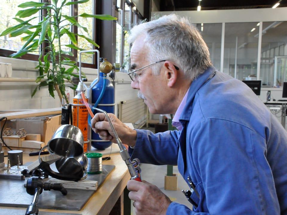Ein Mann macht sich mit einem Lötkolben an einer Tasse zu schaffen