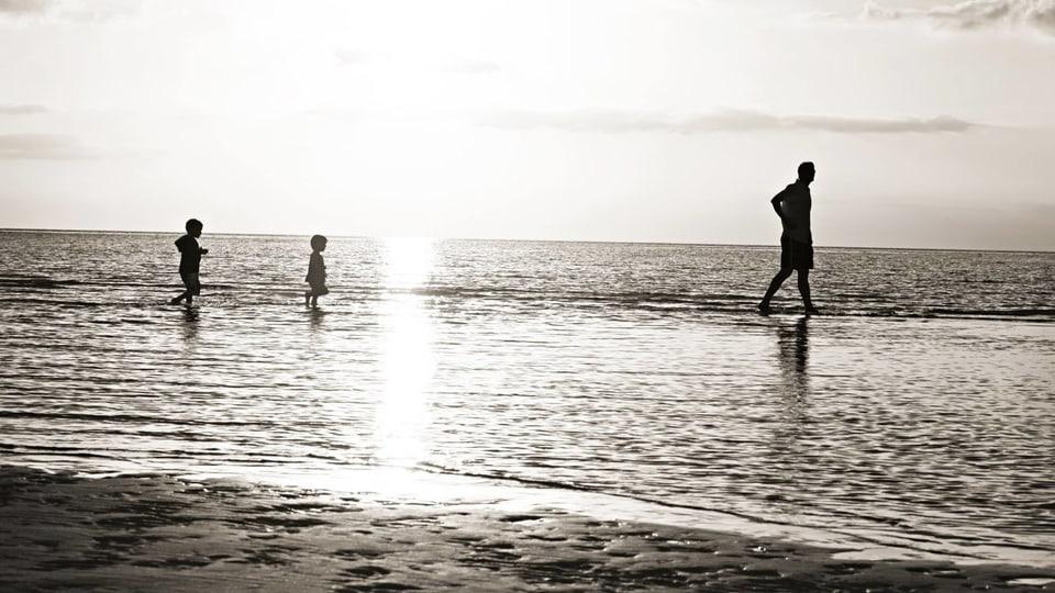 foto ner ed alv dal mar e davant la silhouetta dad in um e dus uffants