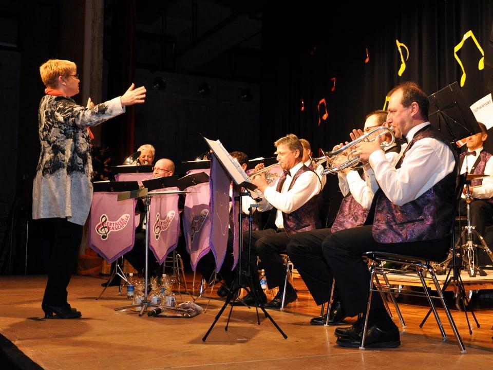 Christine Gertschen gibt auf der Bühne für die Wiggertaler Blaskapelle den Takt an.