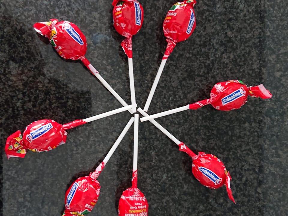 Acht Lollipops sternförmig auf einem Teppich ausgelegt