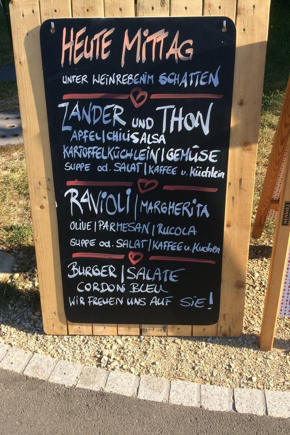 Mittagsmenu vor einem Restaurant. Darauf steht Zander und Thon oder Ravioli.