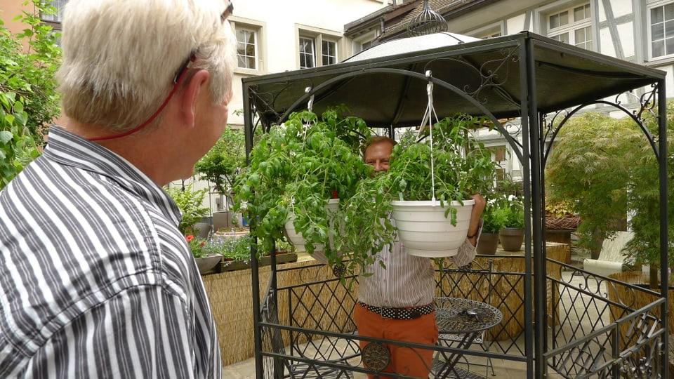 Kurt Aeschbacher bespricht mit Kameramann Peter Ramseier Ideen für aussergewöhnliche Bilder und schaut hinter zwei weissen Ampeln, die mit Grünpflanzen bestückt sind, hervor.