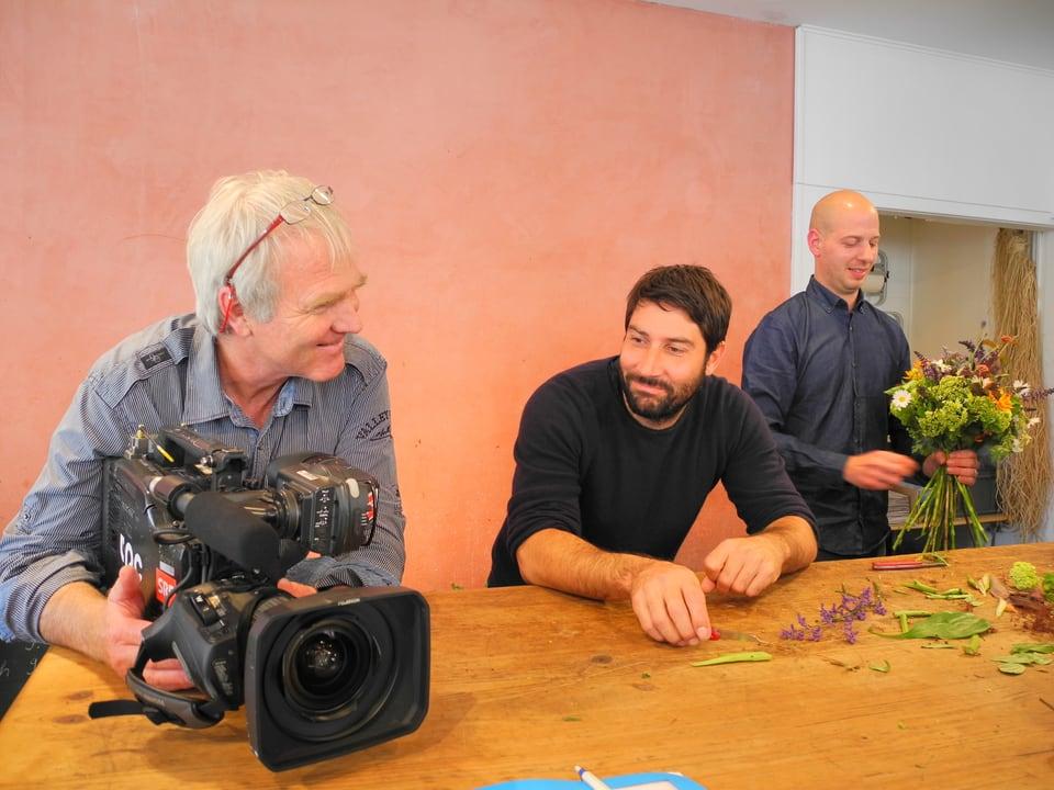 Peter Ramseier hält die Kamera und bespricht mit seinem Berufskollegen Ueli Haberstich die nächste Szene. Im Hintergrund bindet ein Mitarbeiter des Blumenladens Luluderia einen Strauss.