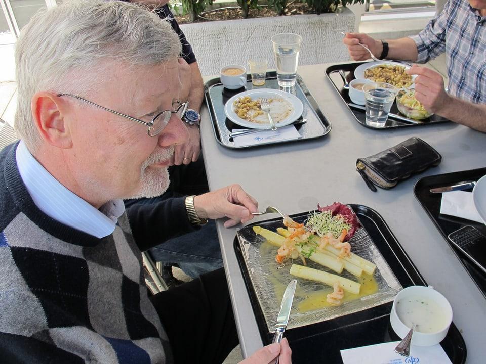 Mann mit Bart sitzt beim Mittagessen. Auf dem Teller hat er Spargeln mit Scampi.