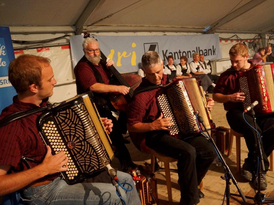Drei Akkordeonisten und ein Kontrabassspieler auf der Bühne.