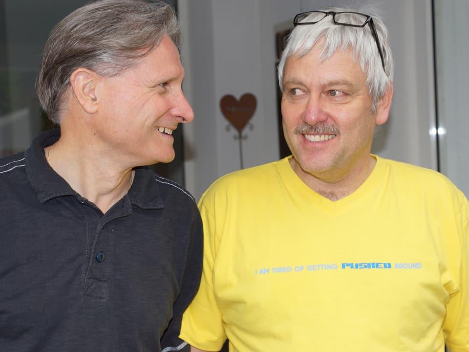 Beat trägt ein schwarzes Hemd, Markus ein gelbes T-Shirt.