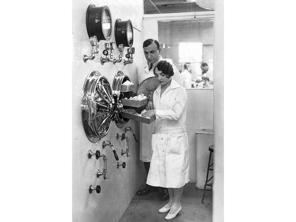 Ein Arzt und eine Krankenschwester an einer futuristischen Apparatur, die an einen Tresor erinnert.