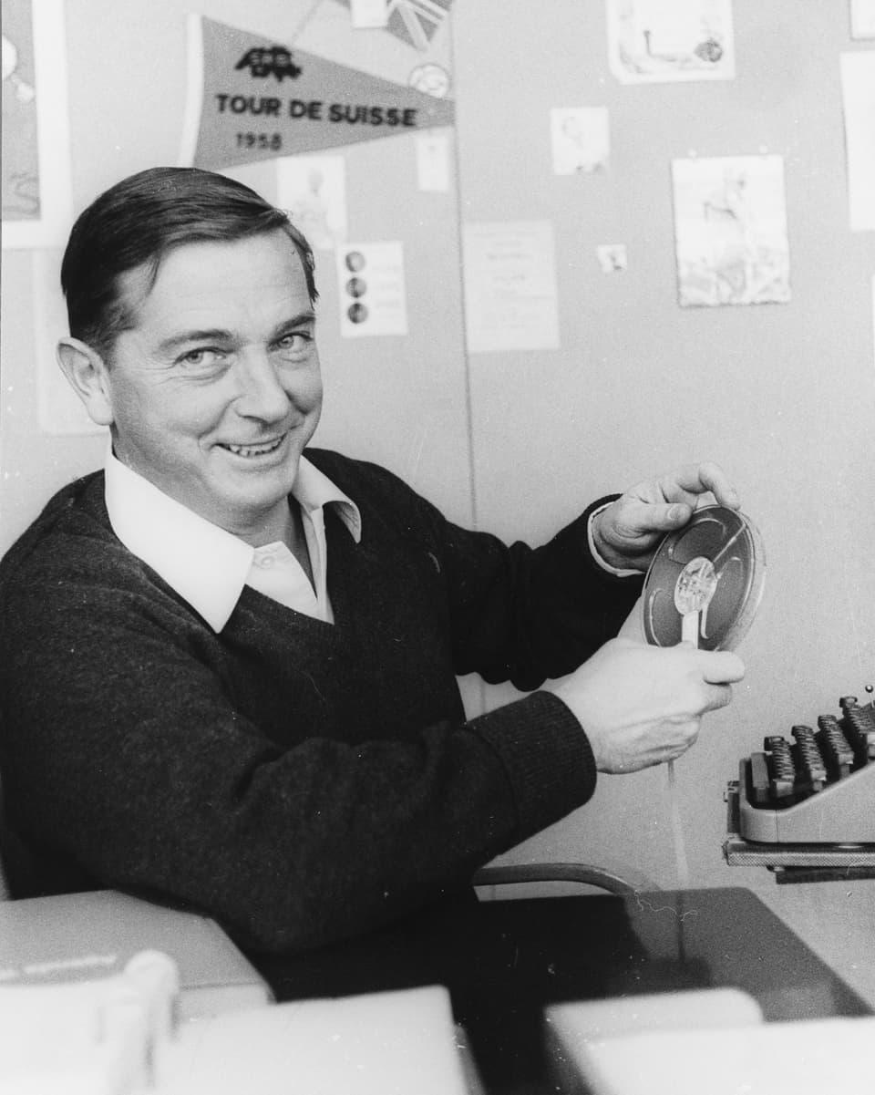 Sepp Renggli mit einer Tonbandspule vor einer mechanischen Schreibmaschine.