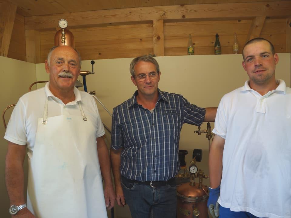 Die drei Männer stehen in einer kleinen Hütte vor antiken Maschinen.