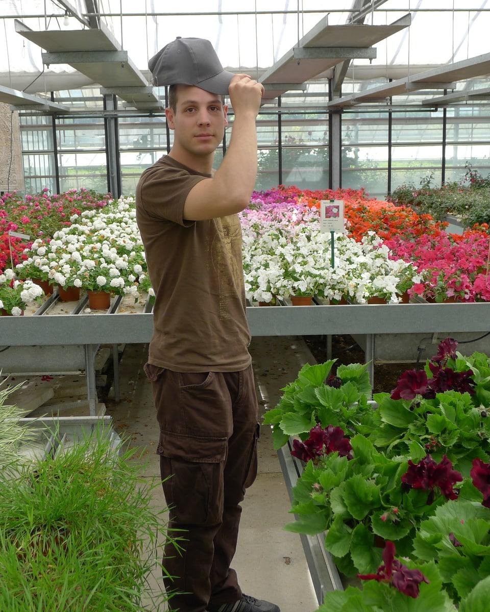 Im Gewächshaus grüsst Beleuchter David Frauenknecht mit seiner Mütze. Vorne sind Ziergräser und Grünpflanzen zu sehen, im Hintergrund eine bunte Farbpalette von Topfpflanzen.