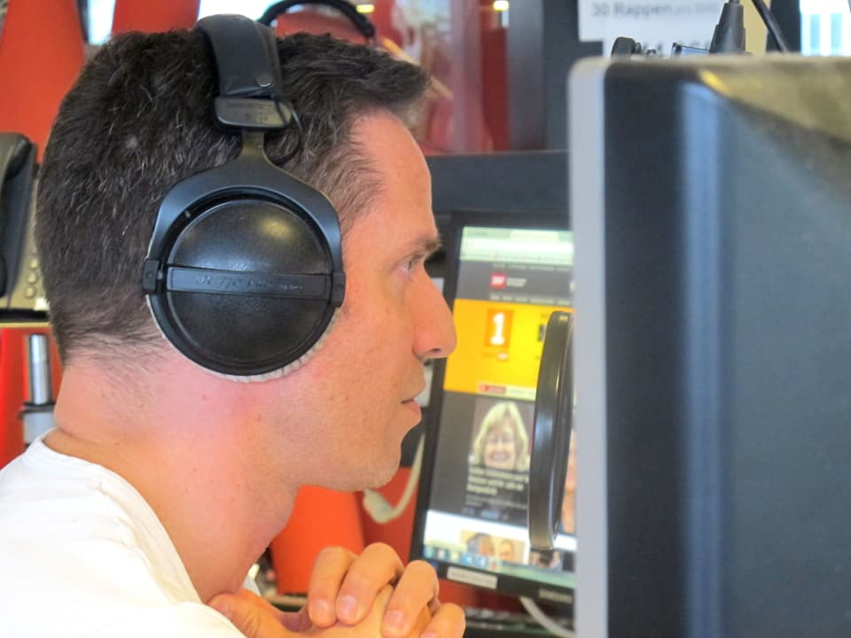 Adrian Küpfer im Studio mit Kopfhörer.
