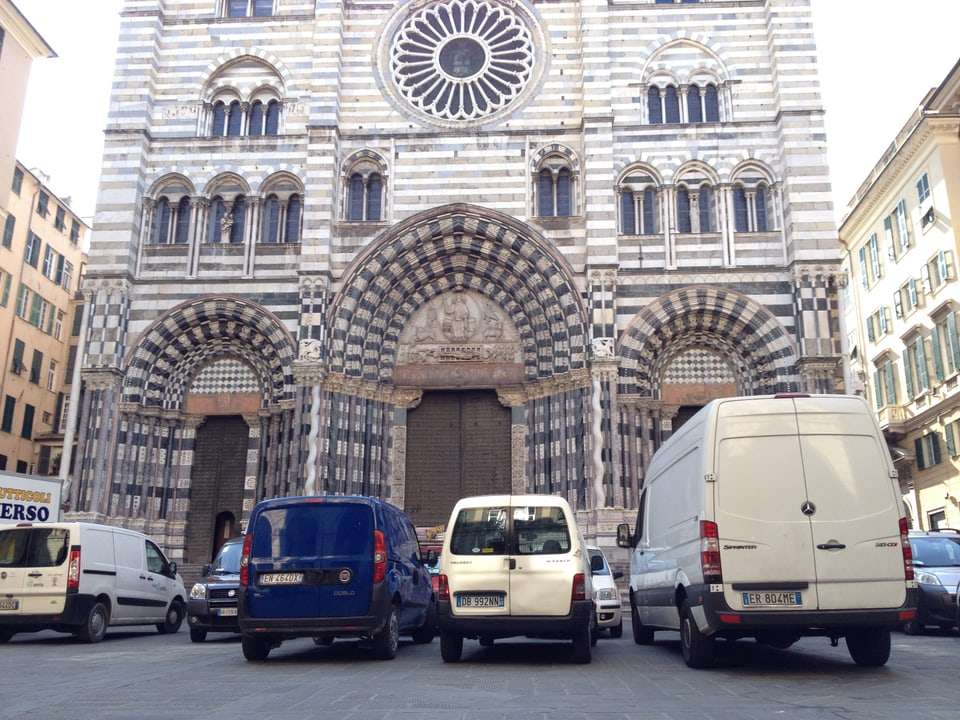 Vista sin il duomo da Genova cun davant plirs autos.