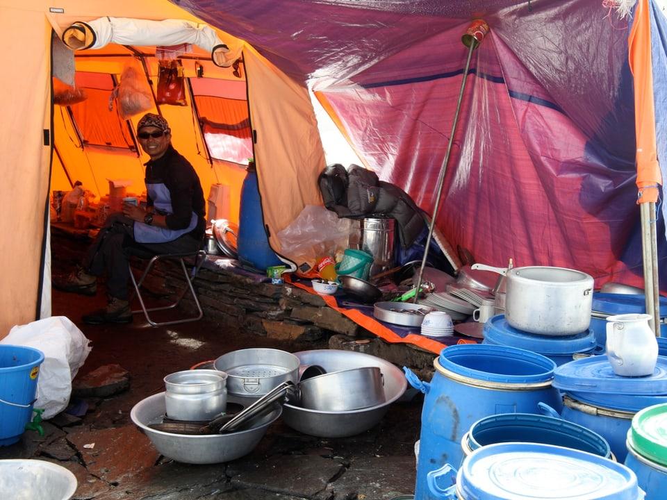 Sherpa sitzt im Küchenzelt. Im Vordergrund Kochtöpfe.