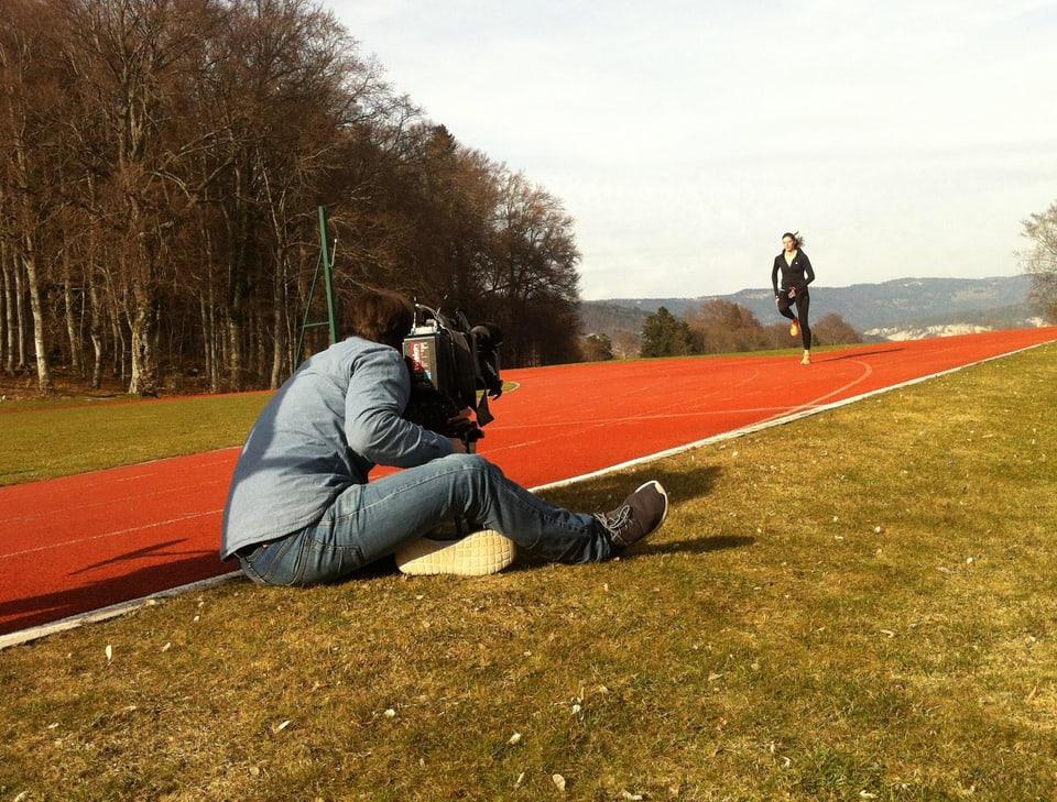 Ein Kameramann filmt eine junge Frau, die auf der Finnenbahn sprintet.