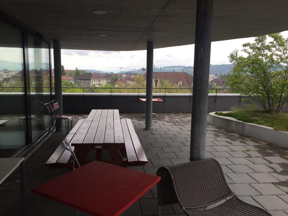 Grosse Terrasse mit Tisch, Stühlen und einem grossen Bank.