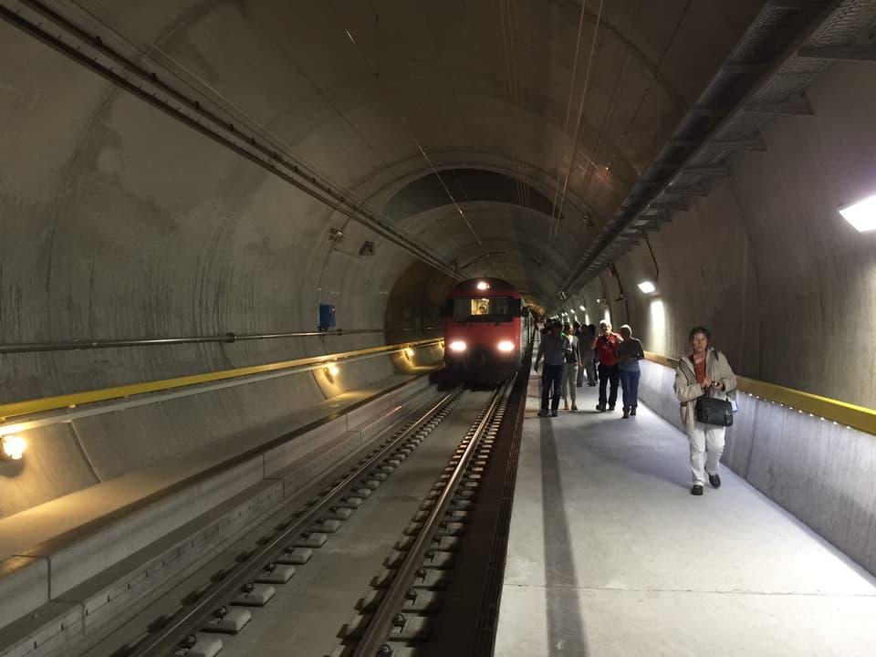Blick in Basistunnel, ein wartender SBB-Zug, ein paar Menschen auf einem Perron