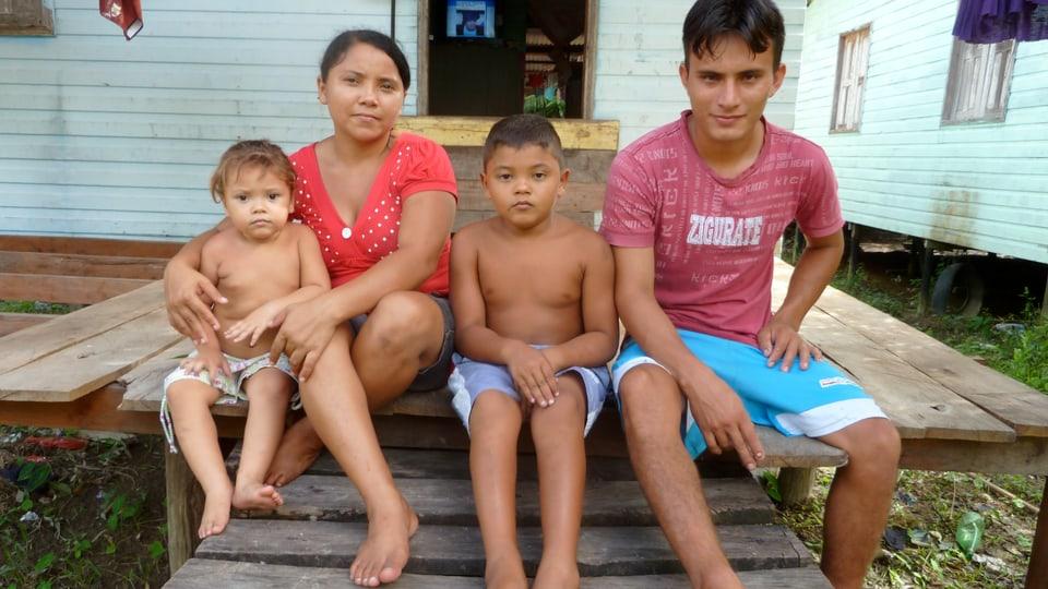 Jeován de Souza und Raimunda Barbosa sitzen mit ihren zwei Kindern auf der Treppe vor dem Haus.