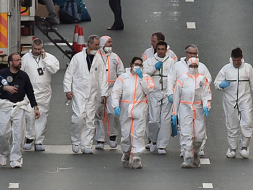 Forensiker in Schutzkleidung gehen auf einer Strasse