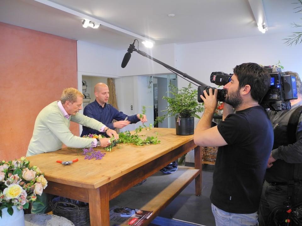 Bei den Dreharbeiten filmt Kameramann Ueli Haberstich Kurt Aeschbacher und Alex Palumbo beim Gestalten eines Gestecks. Diverse Zweige mit grünem Laub werden auf dem hölzernen Arbeitstisch in Form geschnitten. Prominent die Perche (Handstange) des Tonoperateurs Max Büchel.