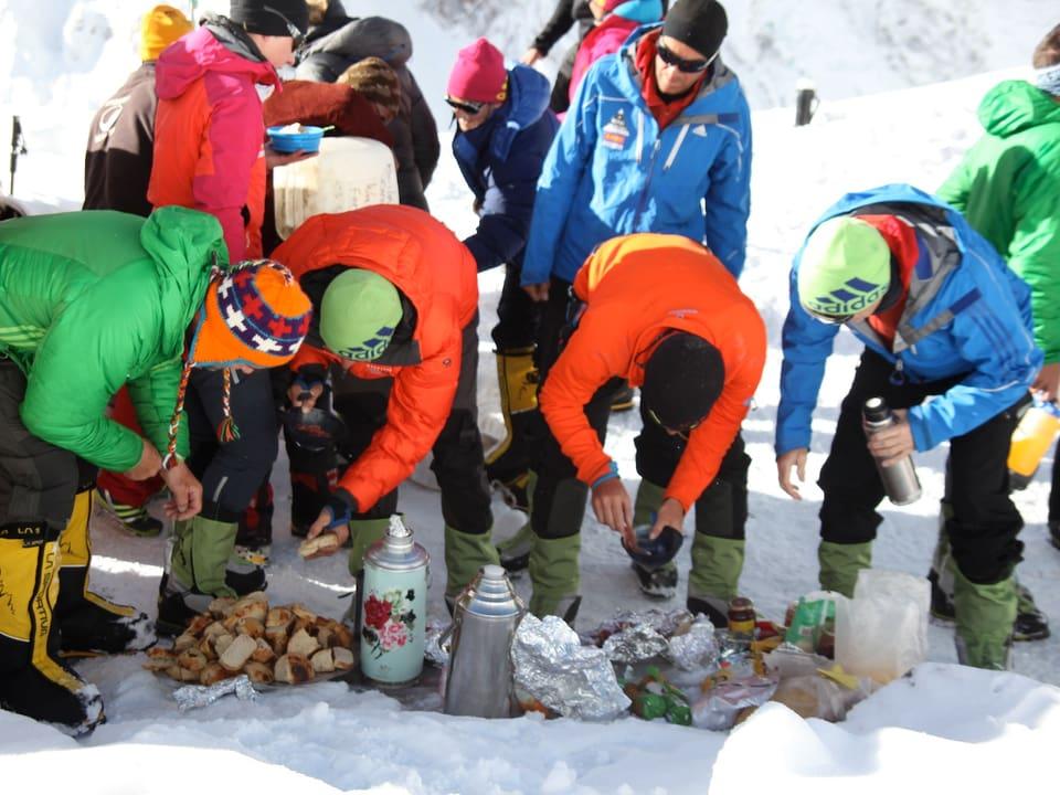 Expeditionsteilnehmer nehmen eine Zwischenverpflegung zu sich. Am Boden liegt Brot und es stehen Thermoskannen herum.