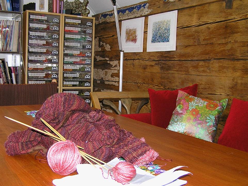 Holztisch mit Sofa, auf dem Tisch eine angefangene Strickete in Rottönen