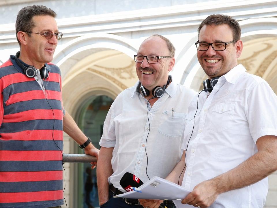 Drei lachende Männer auf einer Konzertbühne.