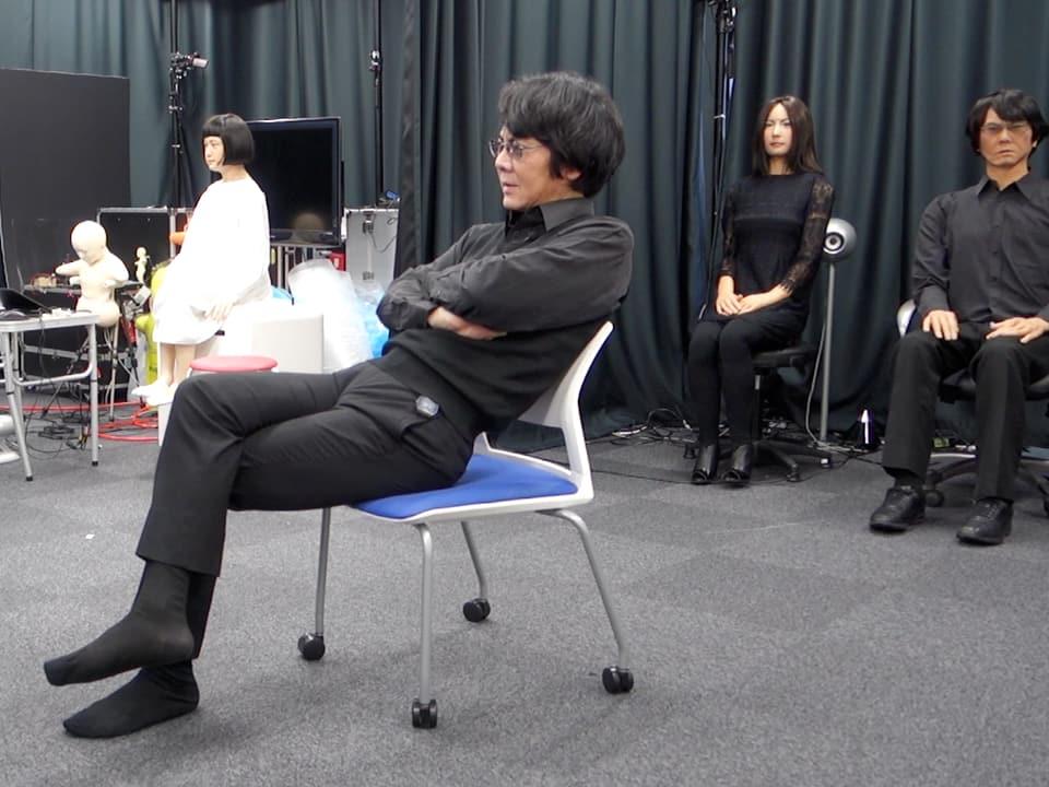 Professor mit Robotern im Hintergrund.