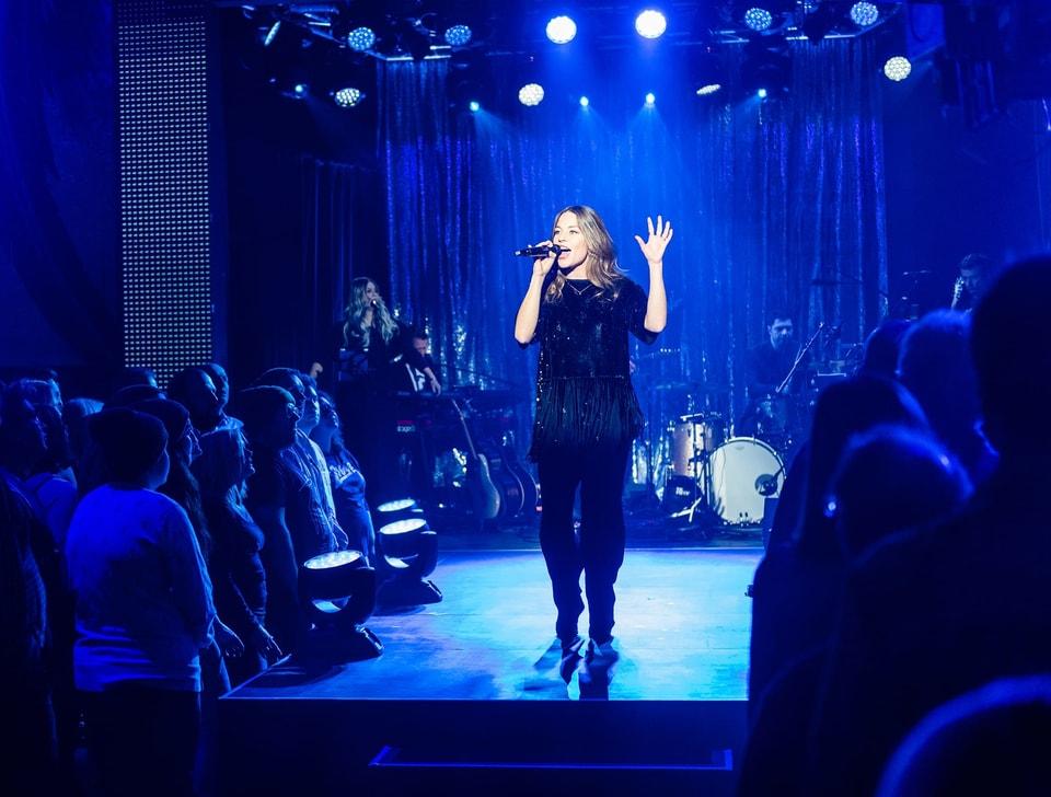 Eine Frau singt auf einer Bühne in ein Mikrofon. Das Publikum schaut gebannt zu.
