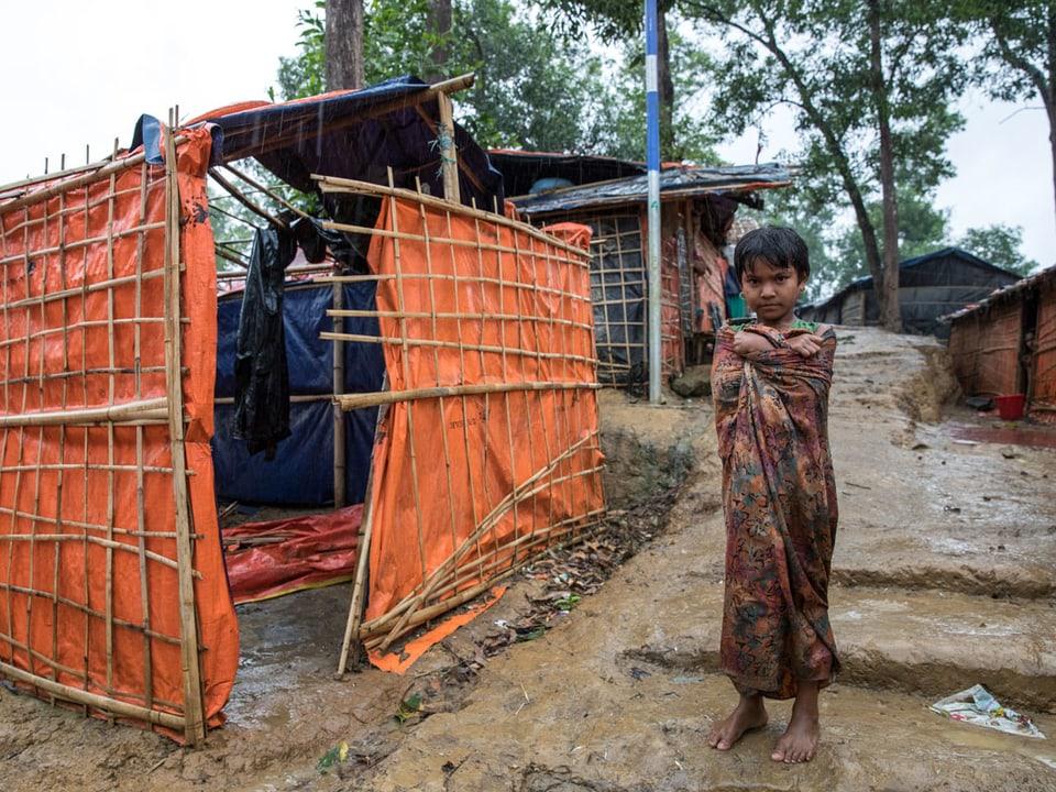 Ein Mädchen steht neben einer Hütte im Regen.