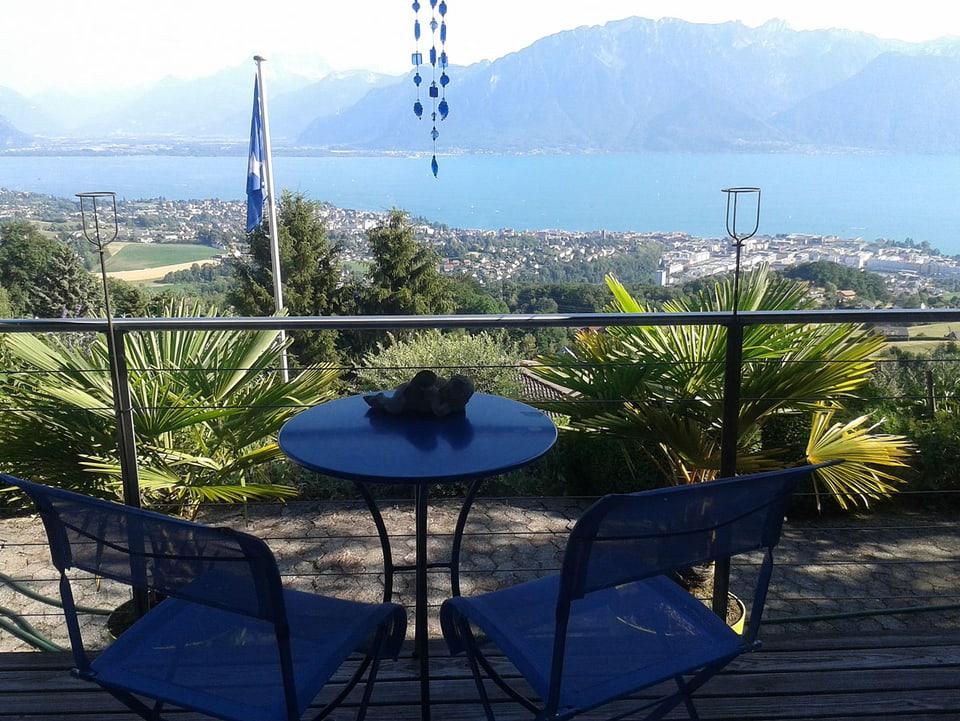 Balkon mit Tisch und zwei Stühlen, im Hintergrund der Genfersee.