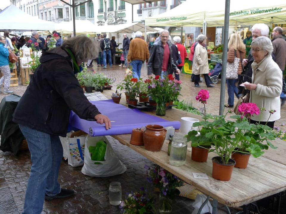 Am Blumenstand schneidet Regula Bänninger auf dem Tisch lila Papier ab einer Rolle in entsprechende Grösse, um einen Blumenstrauss einzupacken. Auf der anderen Seite des Tischs hält die Käuferin das Geld zur Zahlung bereit.