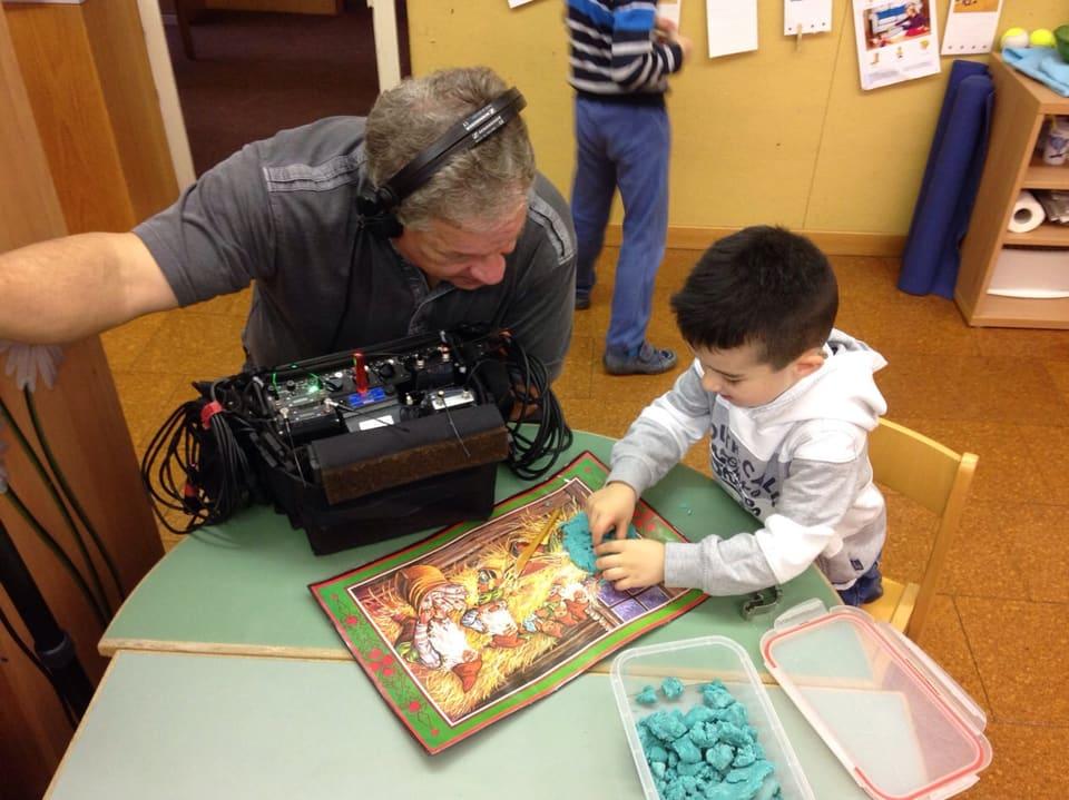 Ein Tonmann unterhält sich am Tisch mit einem kleinen Jungen.