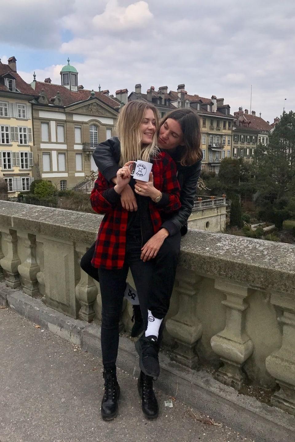 Dominique Rinderknecht und Tamy Glauser auf einer Brücke, mit Tasse in der Hand