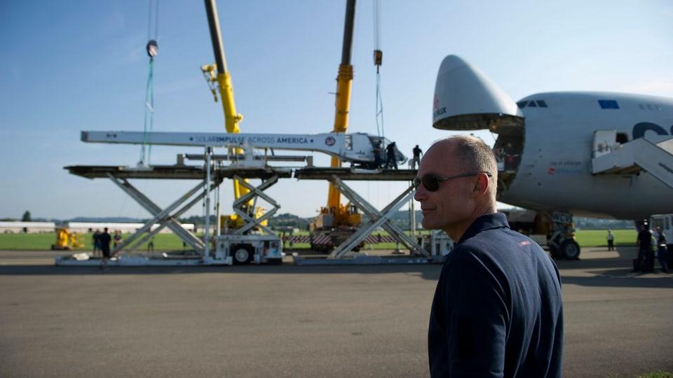 Bertrand Piccard von hinten, das Entladen des Flugzeuges beobachtend.