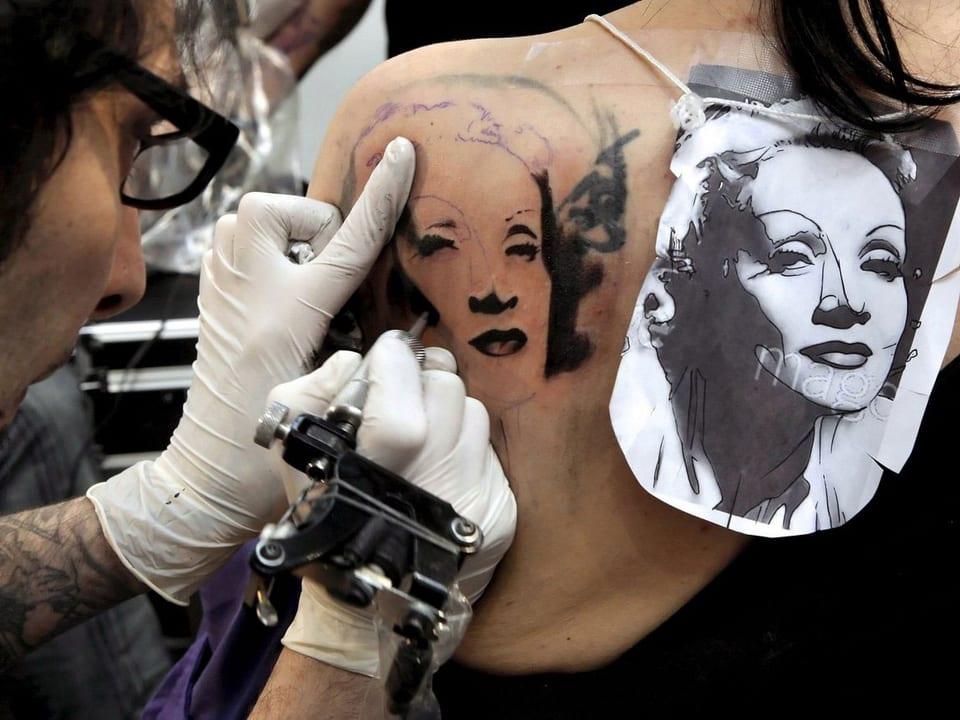 Tätowierer verewigt Marlene Dietrich auf der Schulter einer jungen Frau.