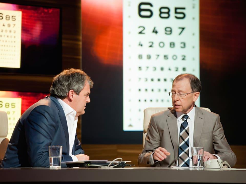 Die Sehtesttafel ist im Hintergrund, vorne diskutieren Giacobbo und Müller.