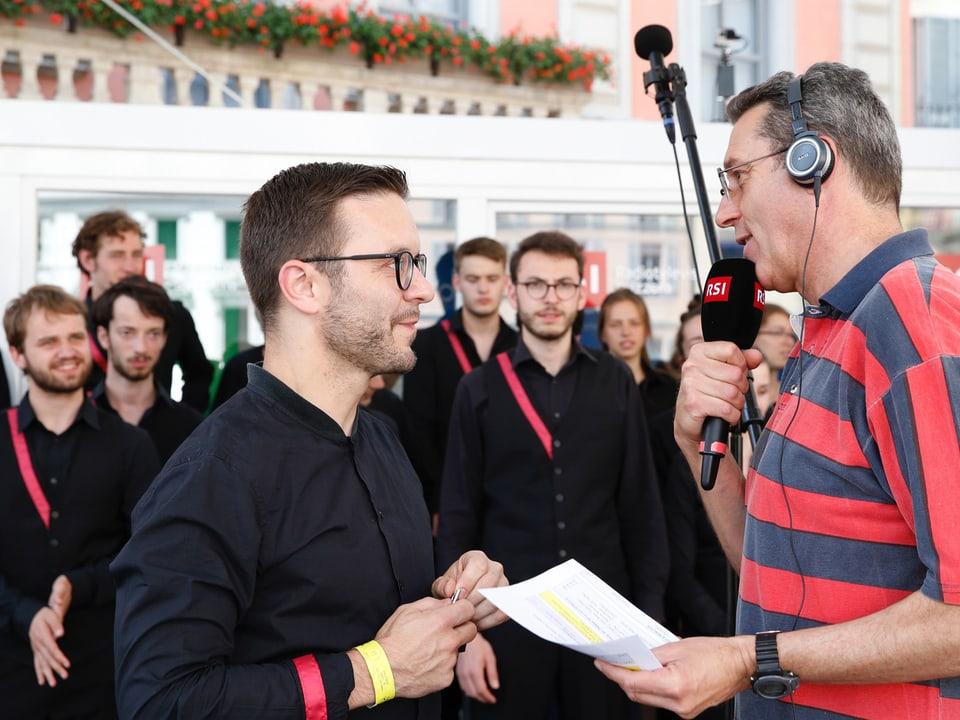 Zwei Männer im Interview vor einer Gruppe Jugendlicher eines Chors.