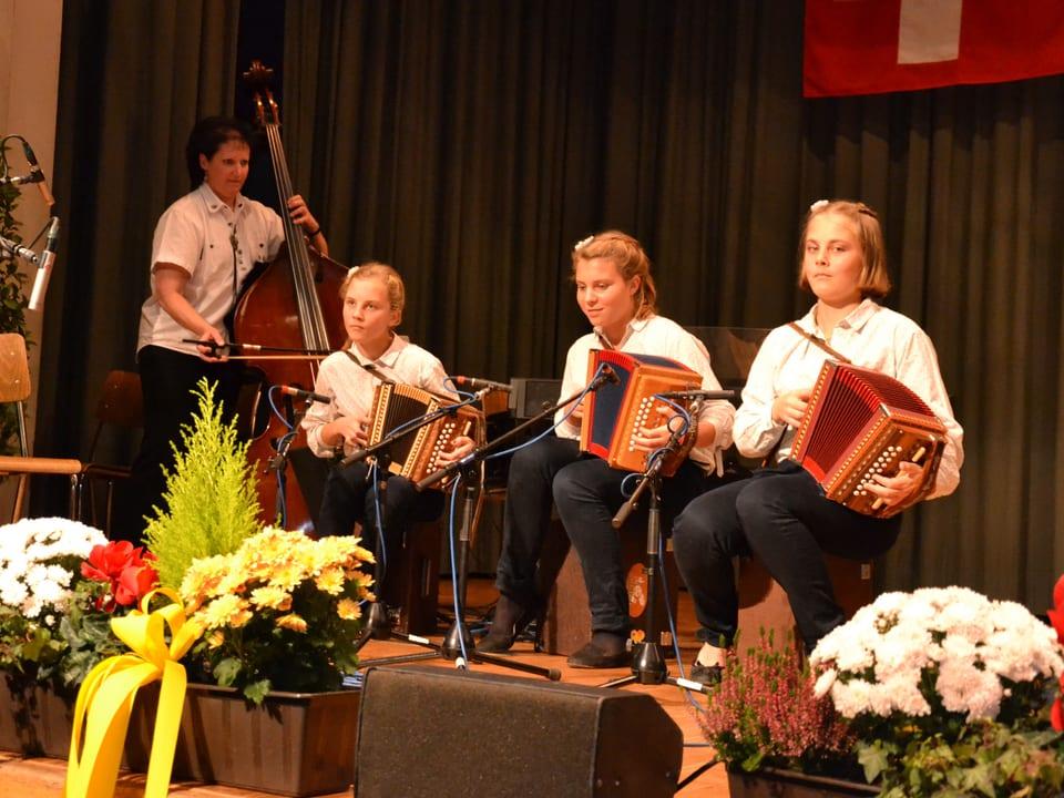 Drei junge Schwyzerörgelispielerinnen werden während des Auftritts von einer Frau am Kontrabass begleitet.