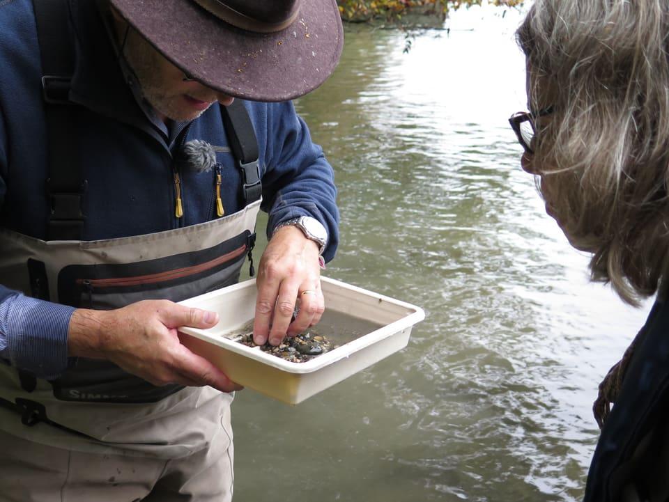Ein Mann durchsucht eine Wanne mit Sand aus dem Fluss.