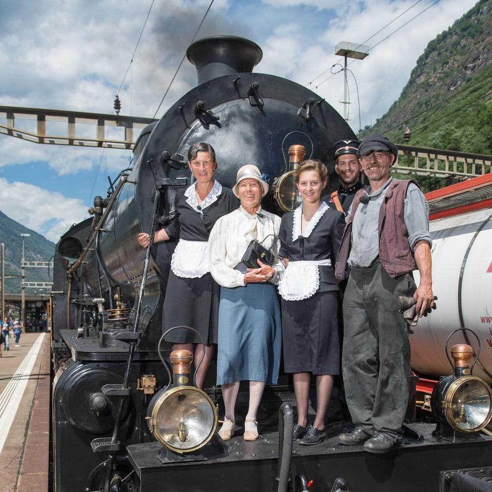 Fünf Personen in historischer Kleidung stehen vor einer schwarzen Dampflok