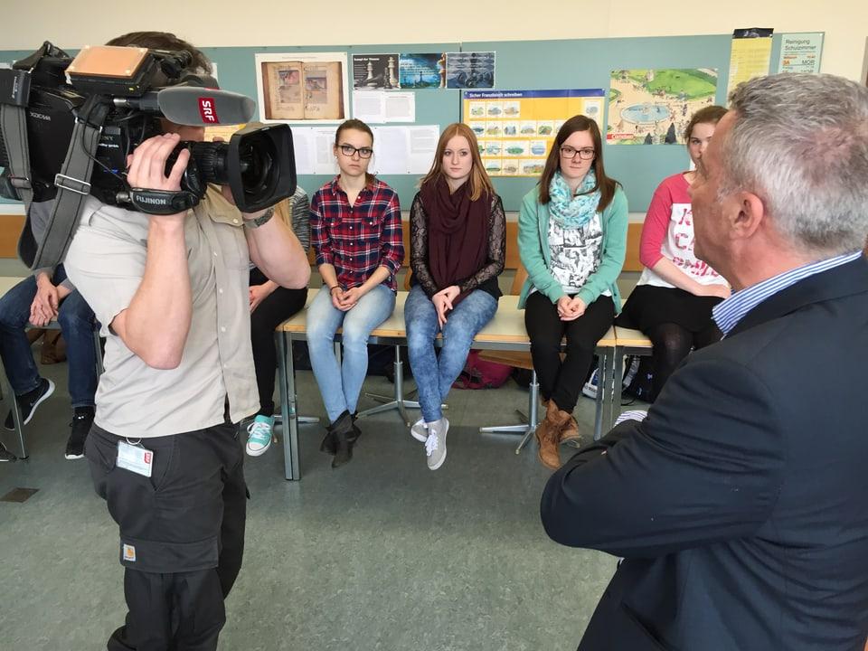 Kamerman filmt mit der Kamera den Moderator. Schülerinnen im Hintergrund