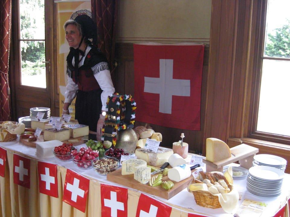 Barbara John in ihrer Sonntagstracht hinter einem Tisch, auf dem eine grosse Auswahl an Schweizer Käse angeboten wird.