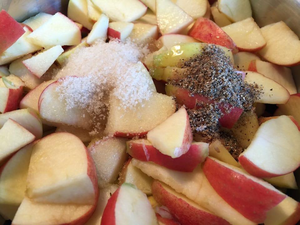 Apfelstücke mit Rohzucker, Honig und Kardamomsamen in der Pfanne.