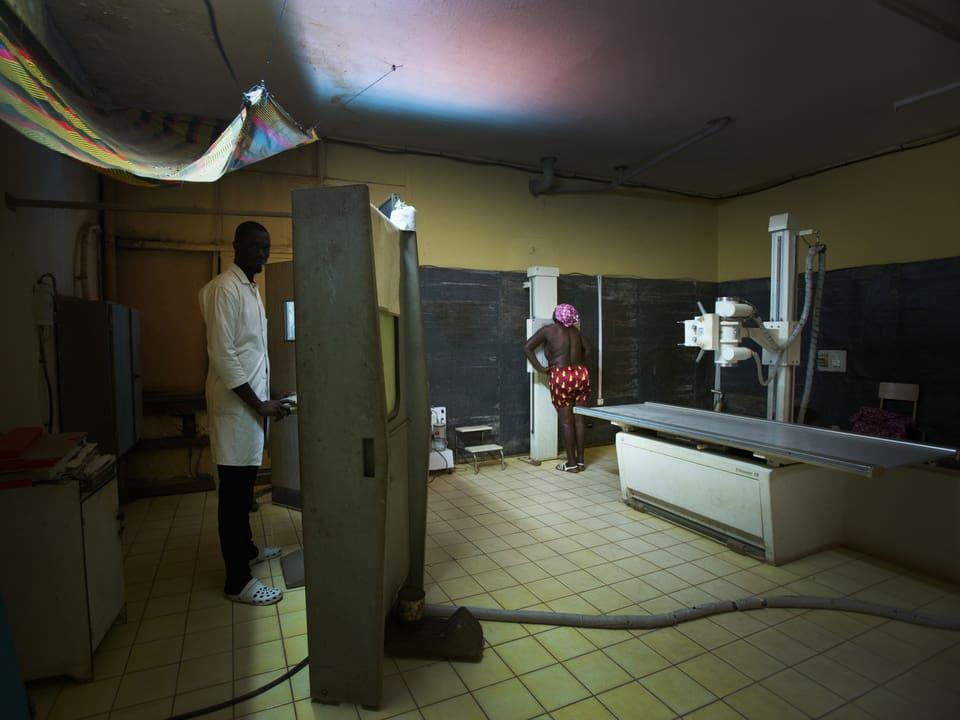 Gefliester Raum, in dem eine Patientin geröntgt wird. Hinter der Schutzwand steht ein Mann, über dem eine bunte Plastikplane hängt.